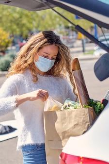 Vrouw met masker die boodschappentassen in de kofferbak van de auto plaatst