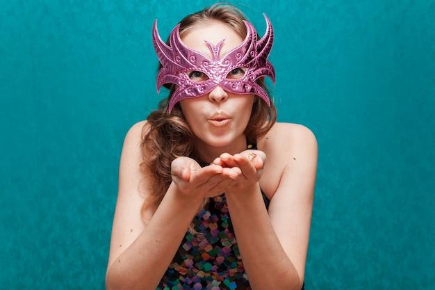 Vrouw met masker die een kus blazen