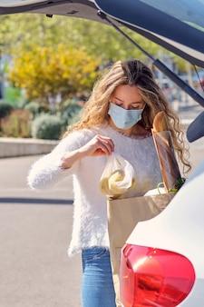 Vrouw met masker die producten in de kofferbak controleert