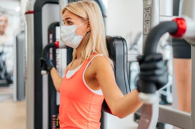 Vrouw met masker en handschoenen bij het uitoefenen van de gymnastiek