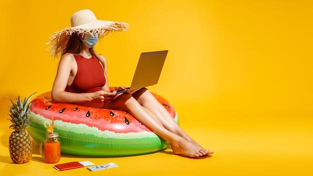 Vrouw met masker en hoed zit op opblaasbare ring terwijl ze online winkelen met creditcard en laptop vasthoudt