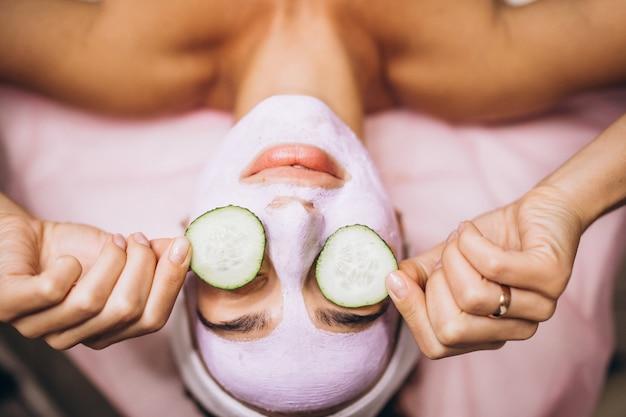 Vrouw met masker en komkommer op haar ogen