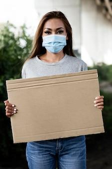 Vrouw met masker en leeg aanplakbiljet