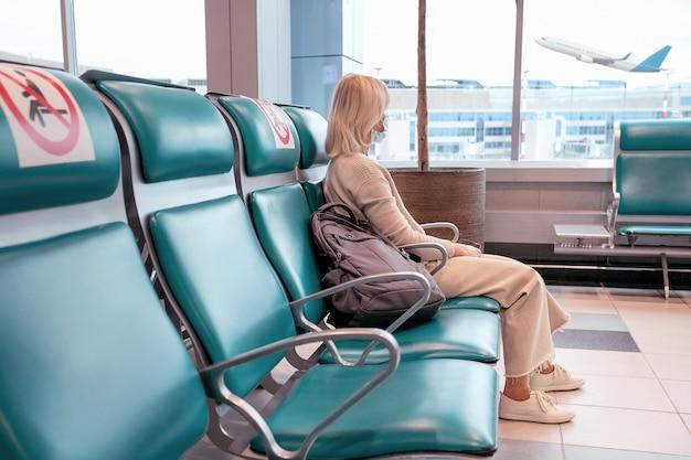 Vrouw met masker kijkt door raam en zit sociale stoel op afstand op de luchthaven. reizen vakantie zakenreis concept. selectieve aandacht.