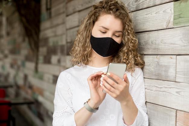 Vrouw met masker met behulp van telefoon