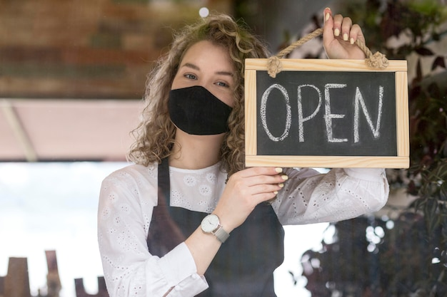 Vrouw met masker met bord met open tekst