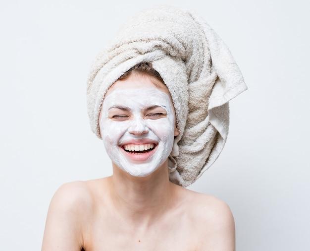 Vrouw met masker tegen zwarte stippen op haar gezichtsemoties met een handdoek op haar hoofd schone huid.