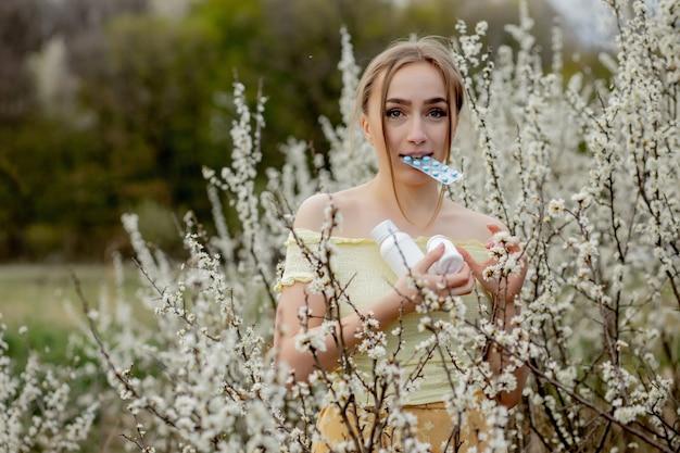 Vrouw met medicijnen in de handen bestrijding van voorjaarsallergieën outdoor portret van een allergische vrouw omgeven door seizoensgebonden bloemen.