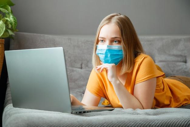 Vrouw met medisch beschermend masker werkt met laptop op kantoor aan huis ligt op de bank. tienermeisje met masker online leeronderwijs via laptop covid 19 lockdown-tijd. werken op afstand tijdens een pandemie van het coronavirus.