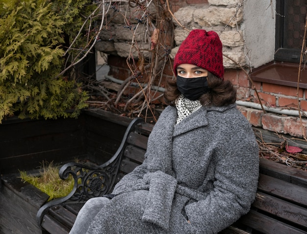 Vrouw met medisch masker buiten op de bank
