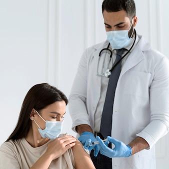 Vrouw met medisch masker dat door arts wordt ingeënt