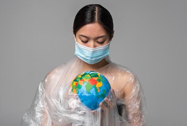 Vrouw met medisch masker die een aardbol vasthoudt terwijl ze is bedekt met plastic