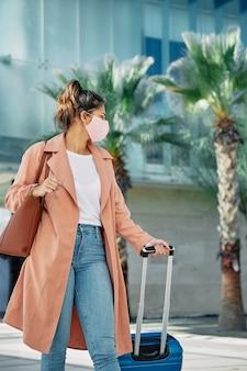 Vrouw met medisch masker die haar bagage vervoert tijdens pandemie op de luchthaven