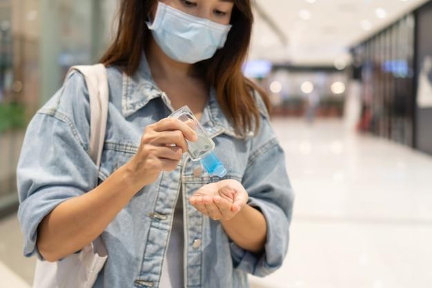 Vrouw met medisch masker die handdesinfecterende gel aanbrengt op desinfectie en haar handen schoonmaakt
