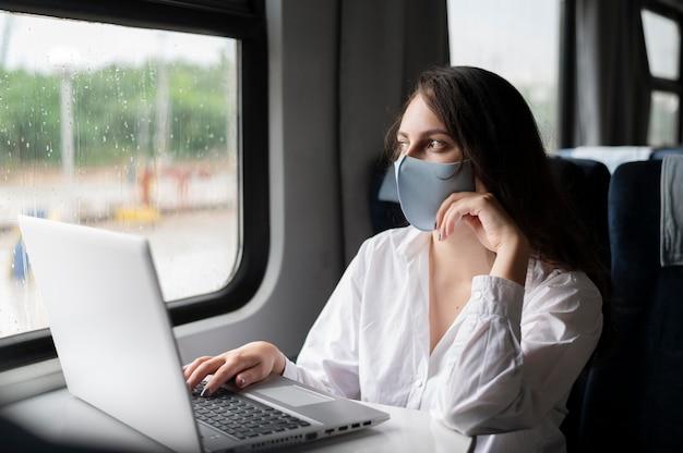 Vrouw met medisch masker die met de openbare trein reist en laptop gebruikt