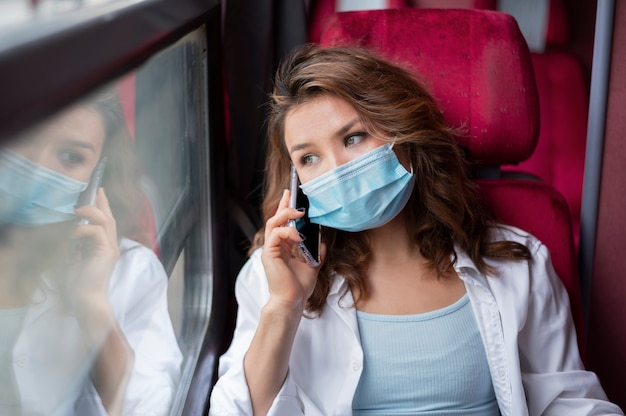 Vrouw met medisch masker die met de openbare trein reist en smartphone gebruikt
