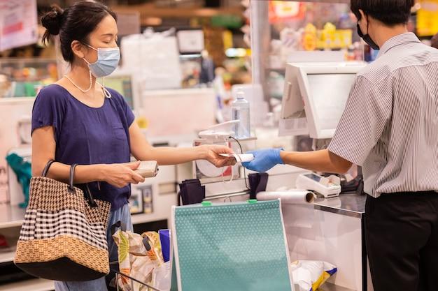 Vrouw met medisch masker die ontvangstbewijs van mannelijke kassier bij supermarkt neemt