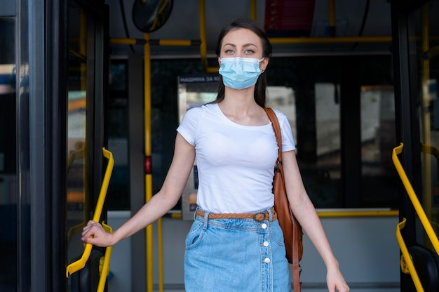 Vrouw met medisch masker die openbare bus gebruikt voor vervoer