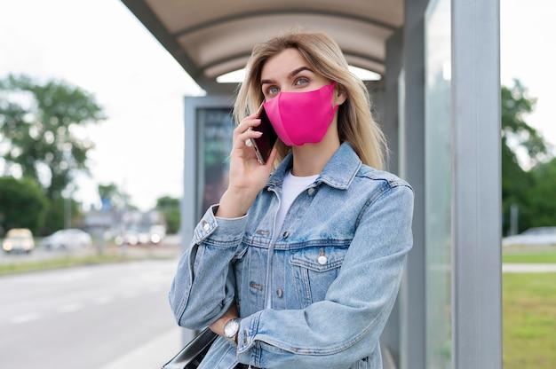 Vrouw met medisch masker die smartphone gebruikt tijdens het wachten op de openbare bus