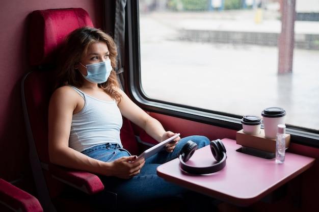 Vrouw met medisch masker die tablet gebruikt tijdens het reizen met de openbare trein