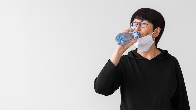 Vrouw met medisch masker drinkwater uit een fles