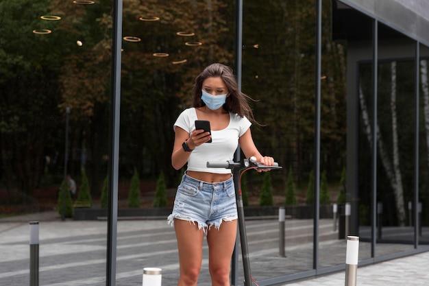 Vrouw met medisch masker en autoped in openlucht