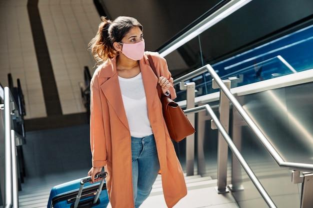 Vrouw met medisch masker en bagage traplopen op de luchthaven tijdens pandemie