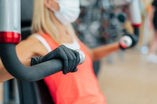 Vrouw met medisch masker en handschoenen bij de gymnastiek het uitoefenen