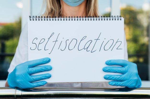 Vrouw met medisch masker en handschoenen die notitieboekje met zelfisolatie houden
