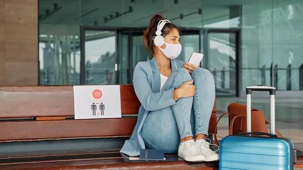 Vrouw met medisch masker en hoofdtelefoons en de luchthaven tijdens pandemie