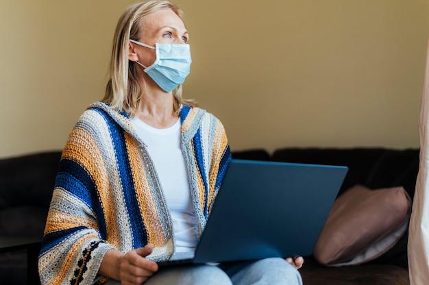 Vrouw met medisch masker en laptop in quarantaine thuis