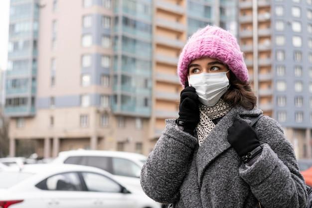 Vrouw met medisch masker in de stad die over de telefoon spreekt