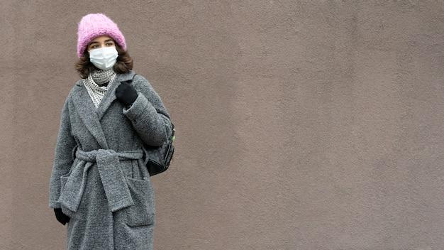 Vrouw met medisch masker in de stad en exemplaarruimte