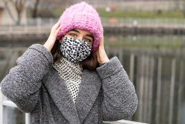 Vrouw met medisch masker in de stad naast meer