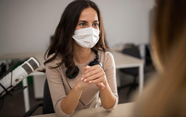 Vrouw met medisch masker in een studio tijdens een radioshow