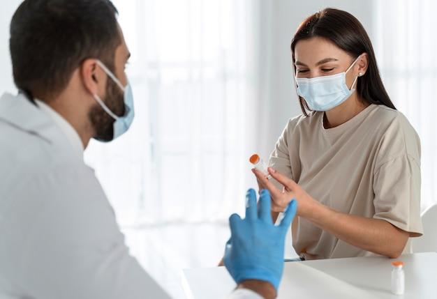 Vrouw met medisch masker in gesprek met de dokter