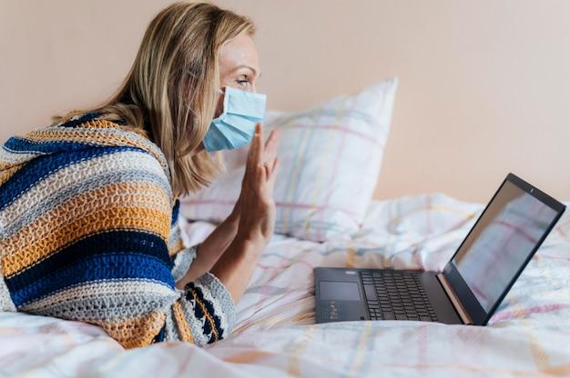 Vrouw met medisch masker in quarantaine thuis met laptop