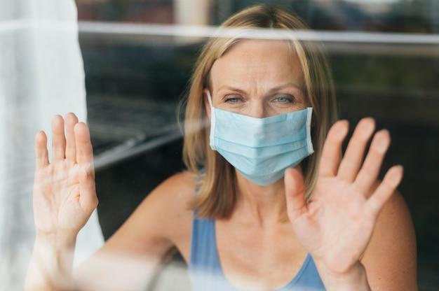Vrouw met medisch masker kijkt door het raam tijdens quarantaine