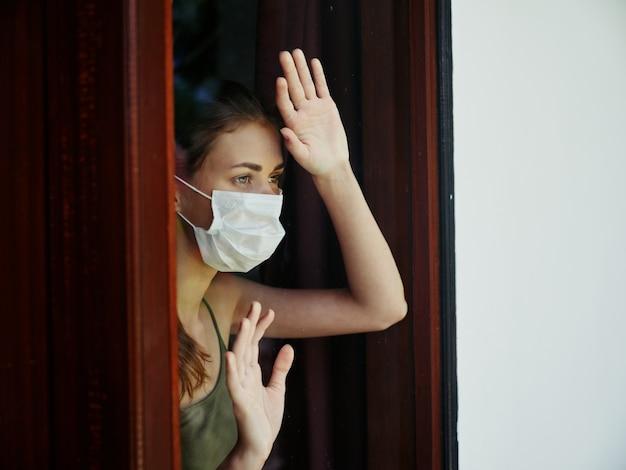 Vrouw met medisch masker kijkt uit raam quarantaine ontevredenheid