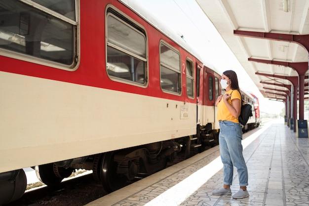 Vrouw met medisch masker klaar om in de trein te komen