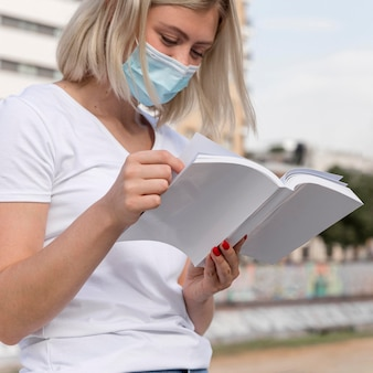 Vrouw met medisch masker leesboek buitenshuis