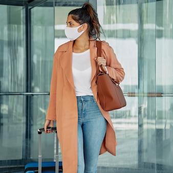 Vrouw met medisch masker met bagage op de luchthaven tijdens pandemie