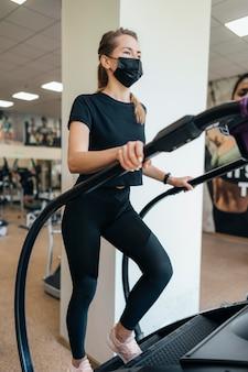 Vrouw met medisch masker met behulp van fitnessapparatuur