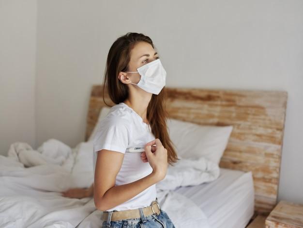 Vrouw met medisch masker met een thermometer onder haar arm en zittend op de gezondheidscontrole van het bed