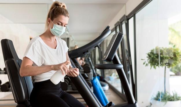 Vrouw met medisch masker met handdesinfecterend middel in de sportschool
