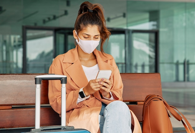 Vrouw met medisch masker met smartphone op de luchthaven tijdens pandemie