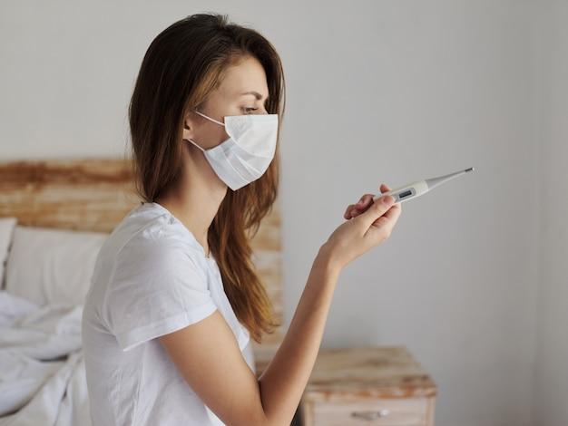 Vrouw met medisch masker met thermometer in handen die temperatuurgezondheid controleert