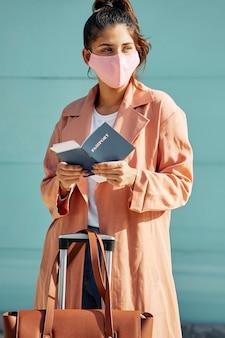 Vrouw met medisch masker op de luchthaven en paspoort tijdens pandemie