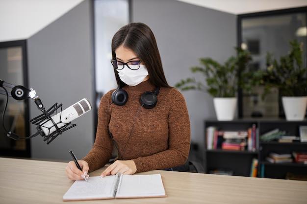 Vrouw met medisch masker op de radio met microfoon en notitieboekje