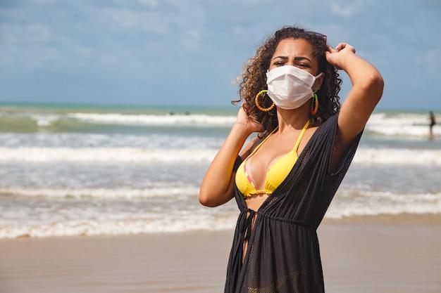 Vrouw met medisch masker op het strand, nieuwe normale regels, webbanner. leven na pandemie, verplicht gebruik van gezichtsmasker in openbare ruimtes, kopieer ruimte